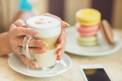 A hot Cup of coffee latte with colorful cookies Royalty Free Stock Photos
