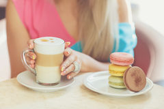 A hot Cup of coffee latte with colorful cookies Stock Photo