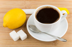 Hot cup of coffee, lemon, knife, spoon and sugar Stock Images