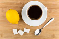 Hot cup of coffee, lemon, spoon and sugar Stock Images