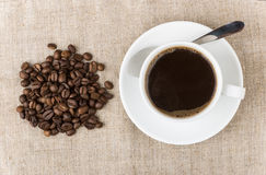 Hot Cup of coffee and scattering of beans Royalty Free Stock Images