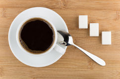 Hot cup of coffee, spoon and sugar on wooden table Stock Photos