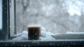 Hot cup of coffee stands on window windowsill in winter cloudy day. In the background blurred tree branches with snow swaying and during snowfall. Seamless stock video footage