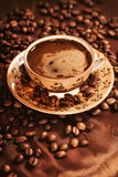 Hot cup of coffee surrounded with coffee beans Stock Photography