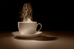 Hot cup of coffee or tea. Hot coffee or tea in a cup silhouette against a dark background