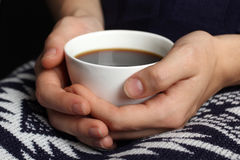 Hot cup of coffee in the women's hands Royalty Free Stock Images