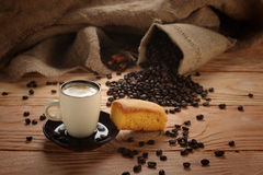A hot cup of espresso with coffee beans and Cake Royalty Free Stock Photo