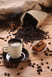 A hot cup of espresso with coffee beans and cinnamon on a wooden Royalty Free Stock Photo
