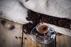 Hot cup of espresso. Cup of hot espresso with coffee beans on wooden background Stock Photography