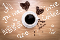 Hot cup of espresso and heart shape made from coffee beans on wooden surface. Sign: All you need is love and more coffee Stock Photography