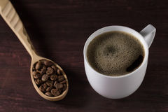 Hot Cup of French coffee on wooden table and a spoon beans. Hot Cup of French coffee on a wooden table and a spoon full of beans Royalty Free Stock Images