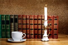 Hot cup of fresh coffee on wooden table with  candle Stock Photo