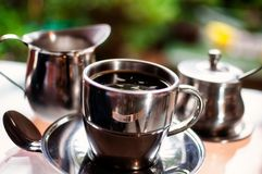 A hot cup of the morning coffee. In a silver cup with pots of milk and sugar in selective focus on a colorful garden bokeh blurred background Stock Photos