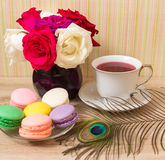 Hot cup of red tea and  colored cakes Stock Photos