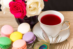 Hot cup of red tea and  colored cakes Stock Photo