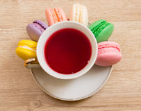Hot cup of red tea  colored cakes Stock Images