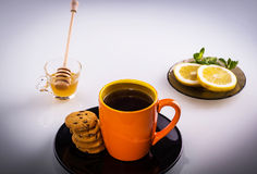 Hot cup of tea with biscuits. Hot tea with biscuits, honey, mint and lemon slices Royalty Free Stock Image