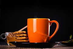 Hot cup of tea with biscuits. Hot tea with biscuits on a plate, honey, mint and lemon slices stock images