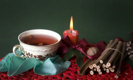 Hot cup of tea with candle and sticks Royalty Free Stock Images