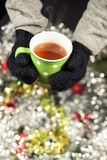Hot cup of tea on Christmas Eve. Hands holding cup of tea on Christmas decoration background Stock Image