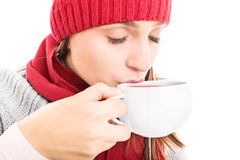 Hot cup of tea. Close-up shot of a young girl wearing winter clothes and drinking a hot cup of tea, isolated on white background Royalty Free Stock Photos