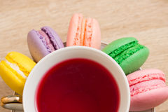 Hot cup of tea, colored cakes and pink flower Royalty Free Stock Photography