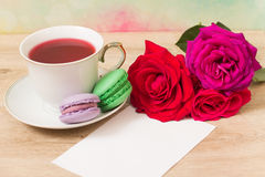 Hot cup of tea, colored cakes and pink flower Royalty Free Stock Image