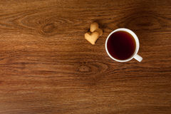Hot cup of tea with cookies on wooden table Stock Images