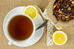 Hot cup of tea and dry herbal leaves Stock Images