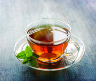 Hot cup of tea with mint leaf on dark rustic background Royalty Free Stock Image