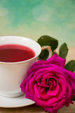 Hot cup of tea  and pink flower Stock Images