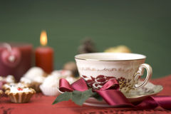 Hot cup of tea with ribbon, cookies and candle Royalty Free Stock Images