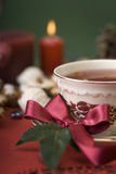 Hot cup of tea with ribbon, cookies and candle Royalty Free Stock Image