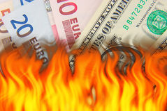 Hot currency. Flame effect over US Dollar and European Euro bank notes Royalty Free Stock Photography