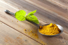 Hot curry. Yellow curry spices in an antique pewter spoon on a wooden table Royalty Free Stock Photos
