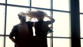 Hot dance two professional dancers. A pair of dancers beautifully dance against the background of a large window closee. Hot dance two professional dancers. slow stock footage
