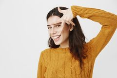 Hot dark-haired caucasian woman with pierced nose showing peace or victory sign over face and smiling broadly while. Standing over gray background in trendy Royalty Free Stock Photos
