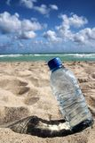 Hot day. Bottle of water on the beach Royalty Free Stock Photo