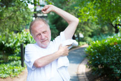 Hot day. Closeup portrait, old gentleman in white shirt wiping sweat droplets dry from body on a hot, sunny, high temperature day, isolated green trees and Stock Photos