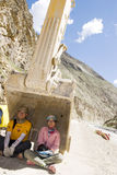 Hot day:Trip to Tibet. Two young men named Shuang Liu and Yali Zhang hide themselves in the gripping device of a grab on a road in Tibet,it is so hot in the wild Stock Image