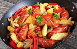 Hot delicious grilled sausages in a wok stock photo