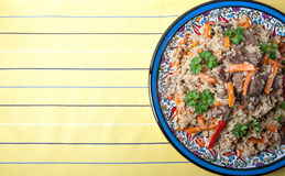 Hot delicious pilaf on a turkish plate on yellow striped tablecl Royalty Free Stock Images