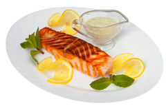 Hot dish of grilled salmon on plate with sauce. Hot dish of grilled salmon on a plate with sauce Stock Photo