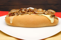 Hot dog. With melted cheese, mushrooms, grilled onions and bacon bets served on withe plate over fancy linen royalty free stock photography