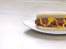 Hot dog. A sausage in a small bread with mustard and onions in a plate stock image