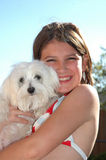 Hot Dog. Young girl smiles and holds her Maltese puppy outside by the pool Royalty Free Stock Photos