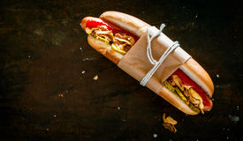 Hot dog with all the trimmings. With a smoked frankfurter, pickles, salad and mustard tied in a brown paper wrapper against a black background with copyspace Stock Photos