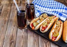Hot-dog américain avec des conserves au vinaigre, des oignons, le ketchup, la moutarde et la soude deux photographie stock libre de droits