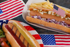 Hot dog and American flag on wooden table Stock Images