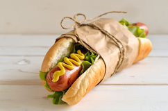 Hot dog. With american yellow mustard and fresh lettuce rolled in a paper and knotted with bow on a light wooden background. Good as a present for  celebration Stock Image